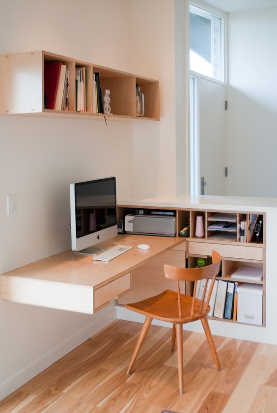 a small modern home office with a floating desk going into an open storage unit, a box shelf and a wooden chair