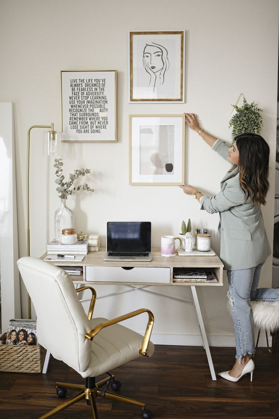 a small modern home office with a lightweight desk, a white chair, a gallery wall and touches of gold plus a basket for storage