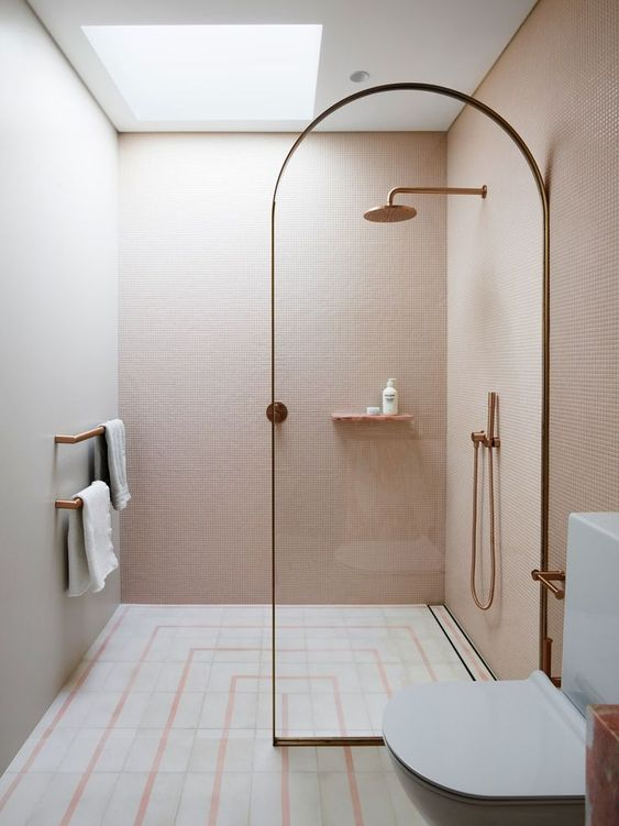 a small unique bathroom clad with blush mini tiles, with neutral and pink ones on the floor and a skylight over the shower plus brass touches