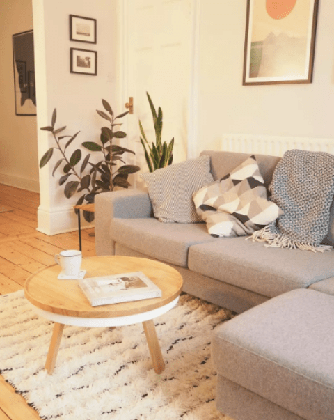 a small warm toned Scandi living room with a grey corner sofa, printed pillows, artworks and a round table plus some potted plants