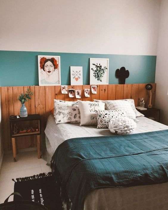 a small whimsical bedroom with a green accent wall and wooden panels, box nightstands, bold artworks and a banner