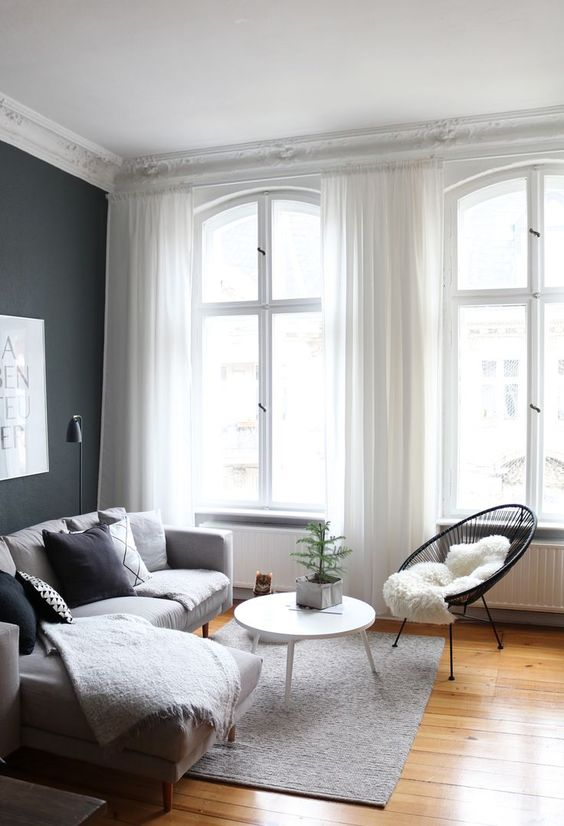 a small yet cozy Scandinavian living room with a black wall, a grey sectional, a black chair, black and white pillows and a round table