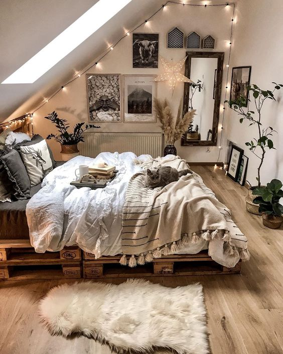 a small yet cozy attci bedroom with a pallet bed, chic and cozy bedding, lights, a gallery wall, a mirror and potted plants
