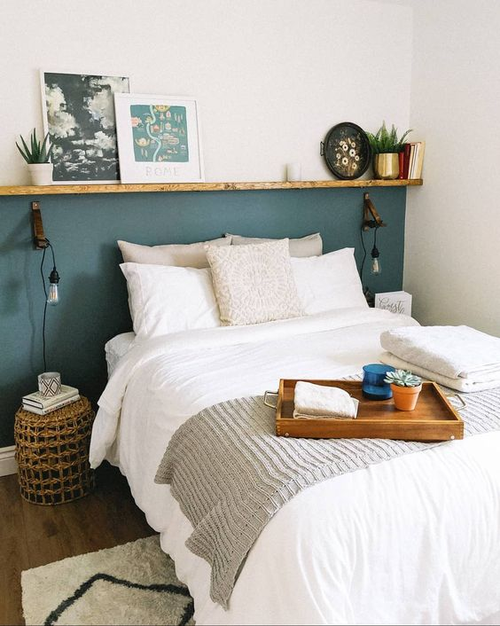 a small yet cozy bedroom with a blue accent wall that is limited with a ledge, a bed, wicker nightstands and some potted plants