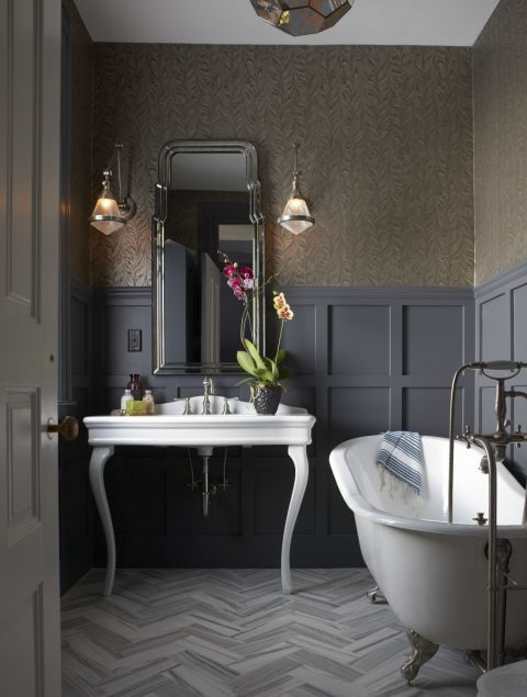a sophisticated vintage bathroom with grey paneling, a free standing sink and a clawfoot tub, grey botanical wallpaper for a moody feel