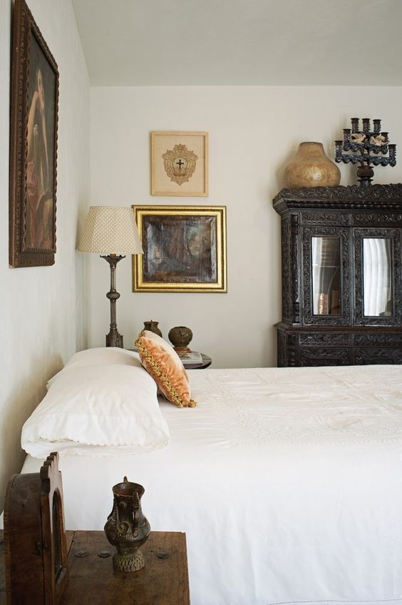 a sophisticated vintage bedroom with heavy furniture, a gallery wall, pretty artworks and lamps is very chic