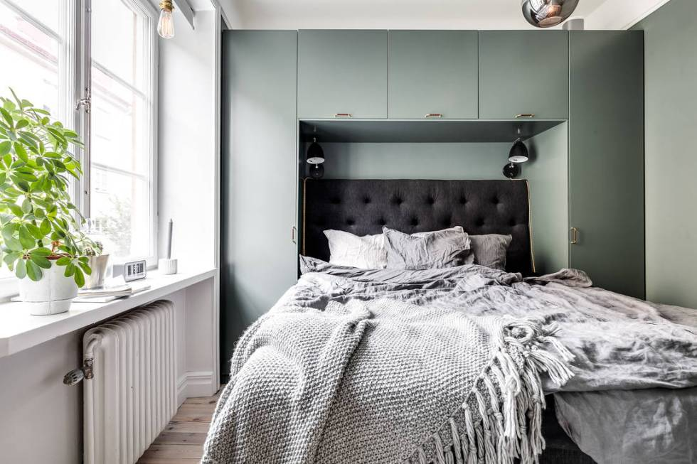 a stylish Nordic bedroom with a green storage unit creating a cozy nook for the bed, some lamps and potted plants