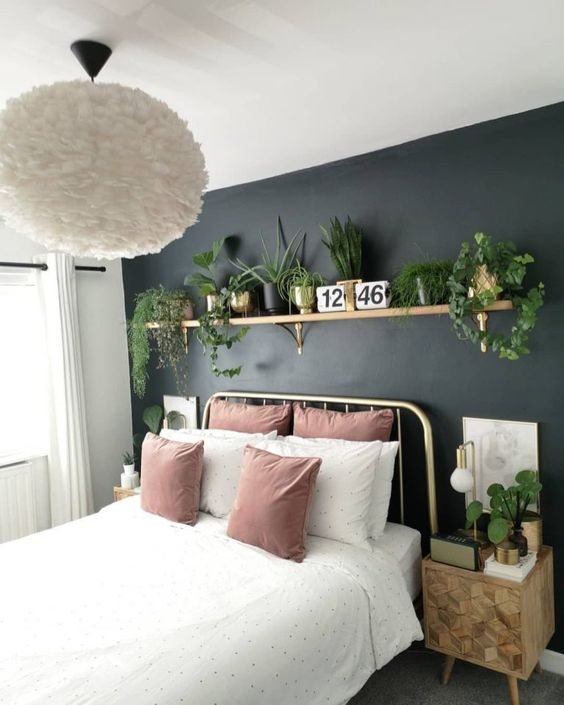 a stylish small bedroom with a black accent wall, a shelf with potted greenery, wooden nightstands and pink touches