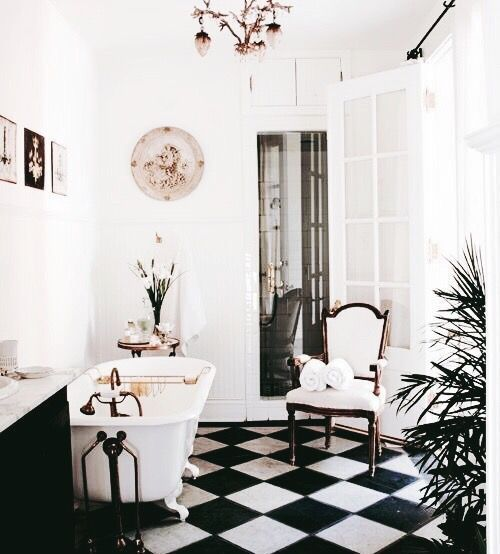 a stylish vintage bathroom with a black and white tile floor, a clawfoot tub, a decorative plate and a floral chandelier is very elegant