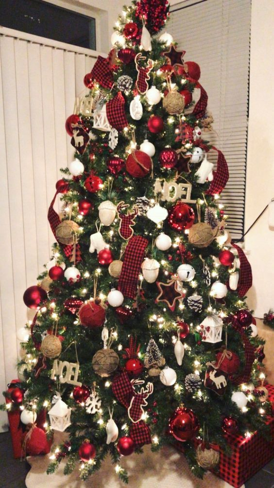 a super bright Christmas tree with plaid ribbons, white and red ornaments, bells, stars, twine baubles and letter decor