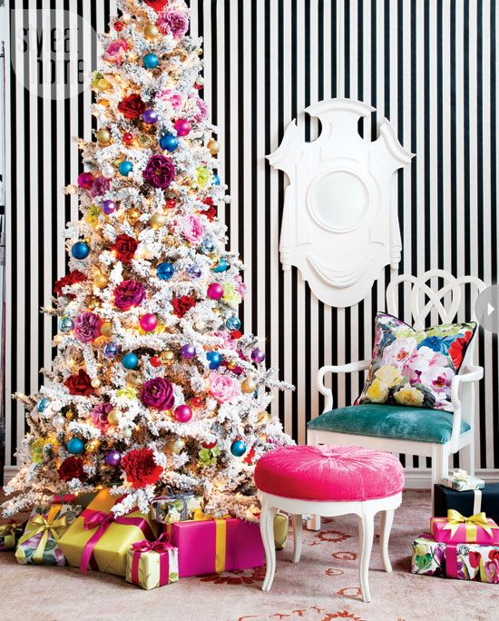 a super bright glam Christmas decor with a white tree with bold ornaments, flowers, lights and colorful gift boxes around