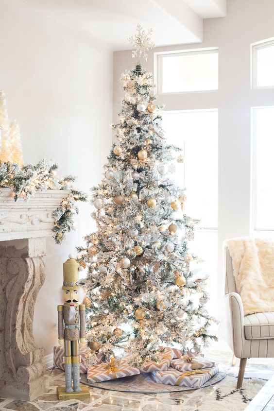 a super glam silver Christmas tree with a snowflake topper pastel and yellow ornaments looks refined