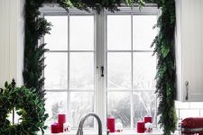 a super lush evergreen garland framing the window instantly brings a holiday feel to the space, and red candles add to it