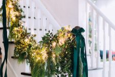 a super lush greenery and foliage garland with oversized hunter green ribbon bows for all-natural Christmas decor