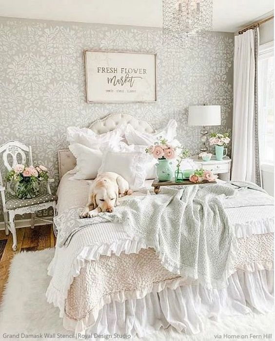 a sweet pastel vintage bedroom with a neutral bed, a crystal chandelier, vintage furniture and beautiful pastel bedding