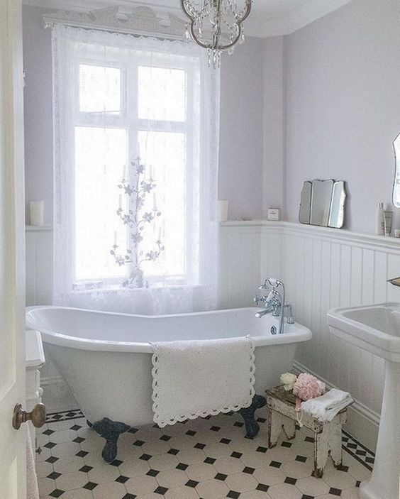 a sweet vintage bathroom with lavender walls and white paneling, a clawfoot tub, a crystal chandelier and a mini stool