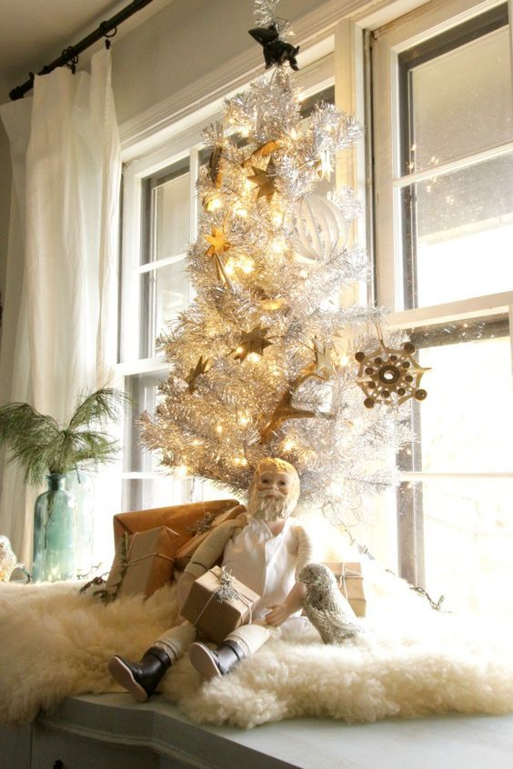 a tabletop silver Christmas tree with lights and vintage gold ornaments and white faux fur to cover it up is a stylish idea