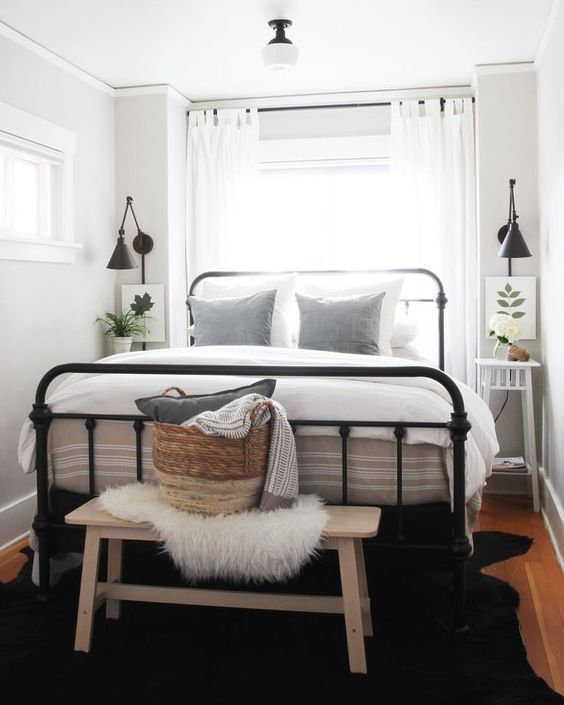a tiny and chic bedroom with a black metal bed, white nightstands, a bench, neutral bedding, artworks and potted plants is chic