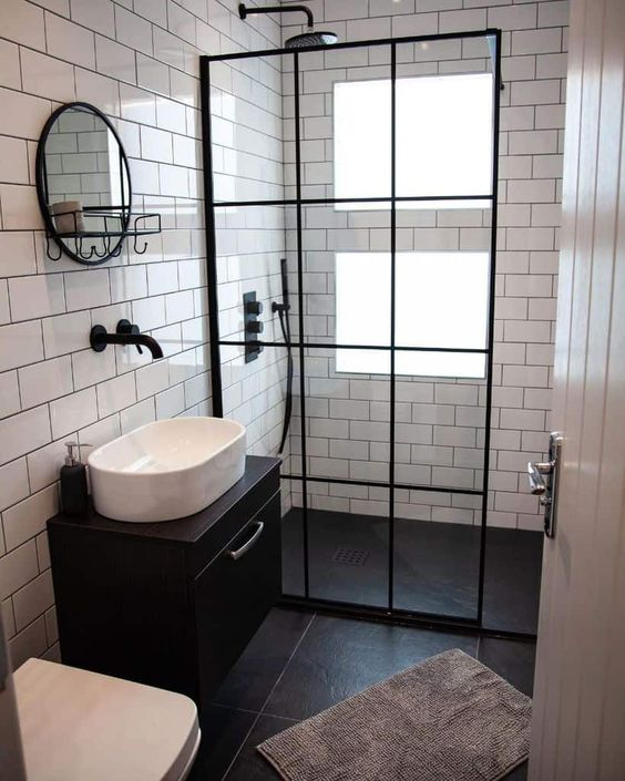 a tiny contrasting bathroom with windows in the shower, clad with white and black tiles, a black floating vanity and black touches here and there
