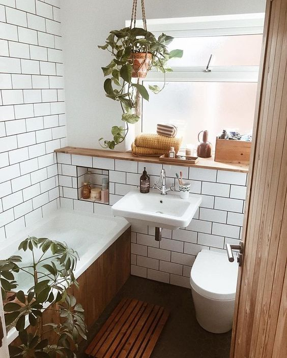 a tiny mid-century modern bathroom with white subway tiles, a bathtub clad with woode, potted greenery and a window