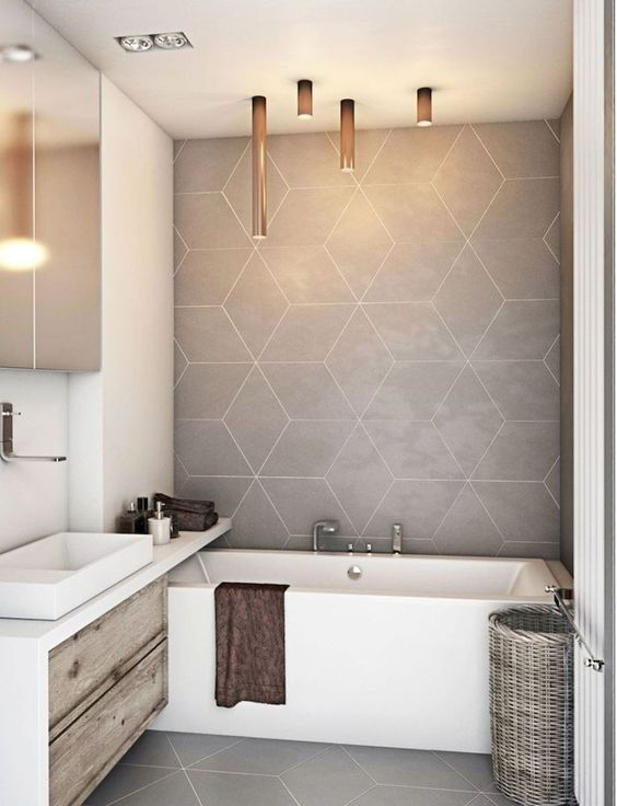 a tiny minimalist bathroom done with grey geometric tiles, a wooden vanity and a long slelf plus catchy tube lamps over the tub