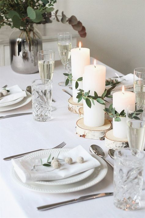 a very neutral and peaceful Christmas tablescape with wood slices as candleholders, greenery, white porcelain and silver cutlery