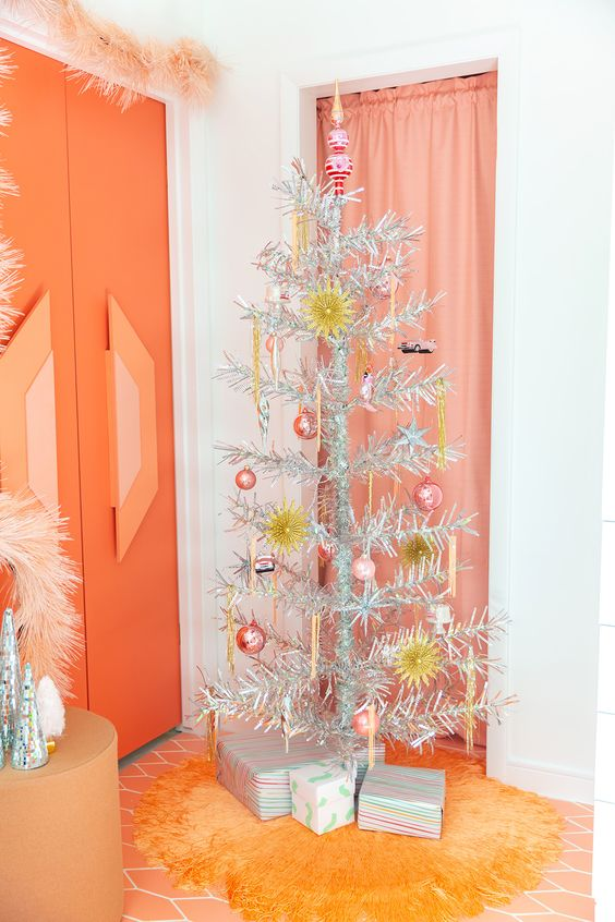 a vintage Christmas tree with pink and yellow ornaments plus icicles is a simple and cool idea for any bright space with a retro touch