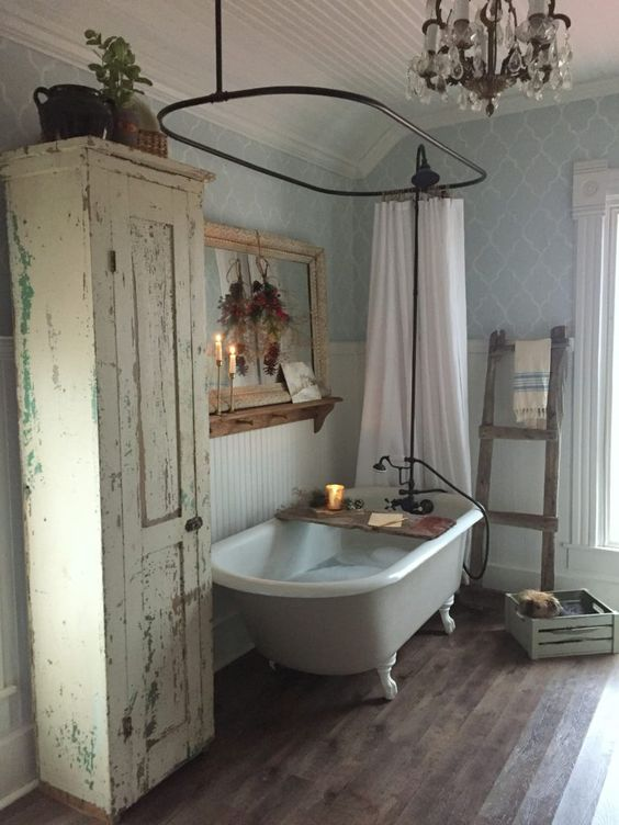 a vintage and shabby chic bathroom with blue wallpaper, a clawfoot tub, a mirror with a shelf and a shabby chic cabinet