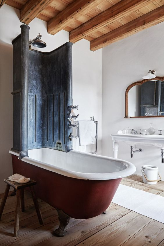 a vintage bathroom with a wooden floor and ceiling, a red clawfoot bathtub and a metal detail on it plus a large free-standing sink