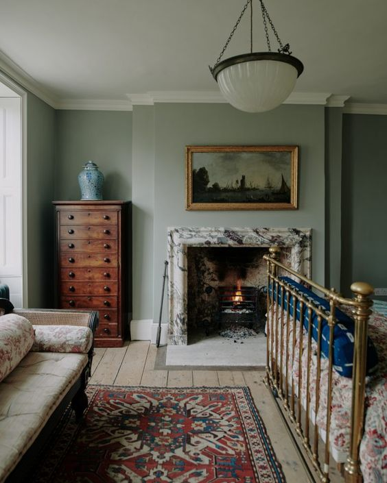 a vintage bedroom with a marble clad fireplace, a metal bed, vintage furniture, a pritned rug and a pendant lamp