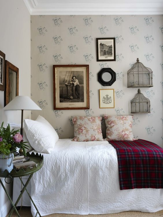 a vintage bedroom with floral wallpaper, a vintage gallery wall, a metal nightstand and blooms is a lovely space