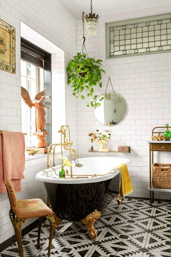 a vintage black and white bathroom with a geometric floor, a black clawfoot tub, a crystal chandelier, potted greenery and a chic stool