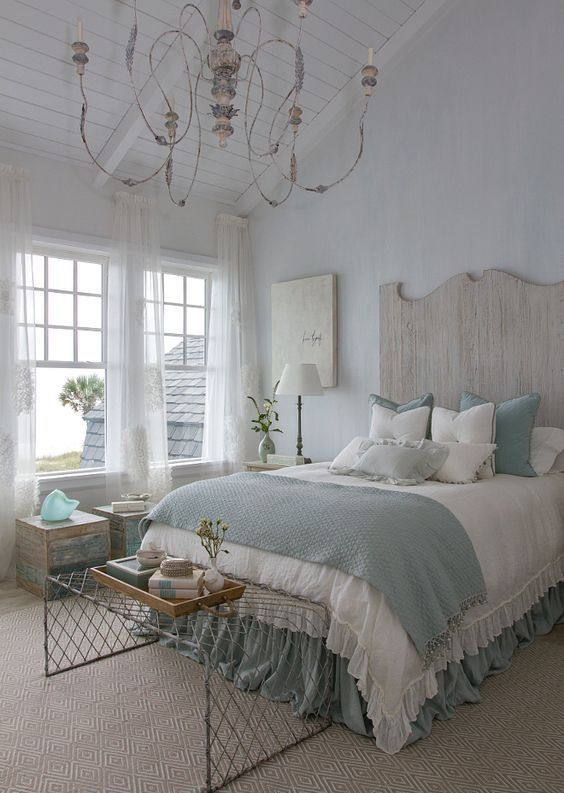 a vintage coastal bedroom with a bed with a carved headboard, a wire bench, a vintage chandelier and touches of light pink