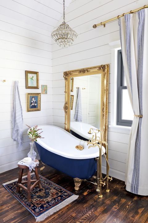 a vintage farmhouse bathroom clad with beadboard, with a blue clawfoot tub, an oversized mirror and a crystal chandelier plus a boho rug