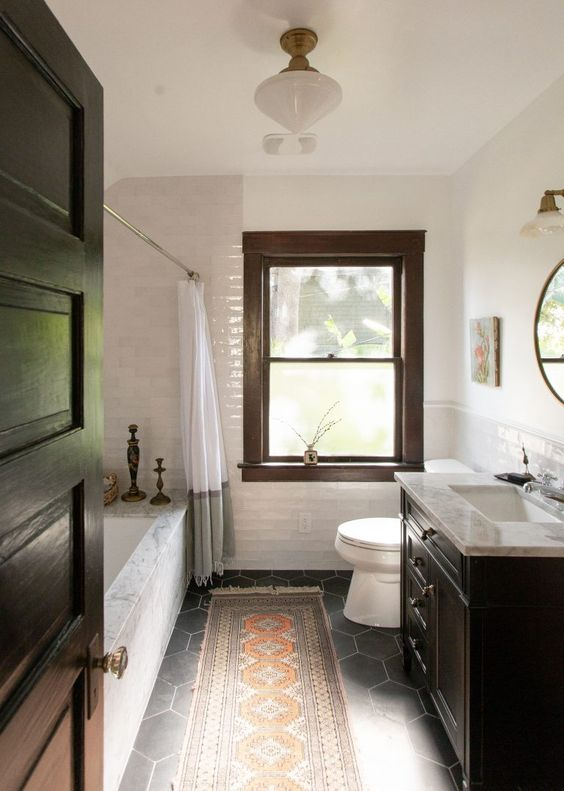 a vintage farmhouse bathroom with a black vanity, a marble clad tub, a boho rug and vintage lamps and sconces