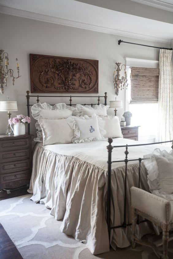 a vintage farmhouse bedroom with a metal bed, heavy nightstands, chic wall scocnes and neutral bedding plus a carved artwork