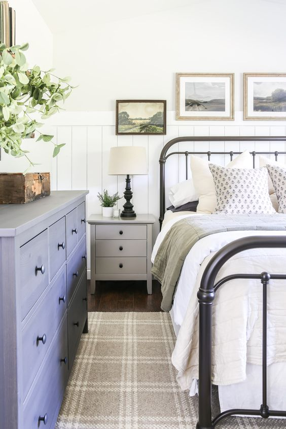a vintage farmhouse bedroom with beadboard, a metal bed, a blue dresser, a gallery wall and potted greenery is stylish