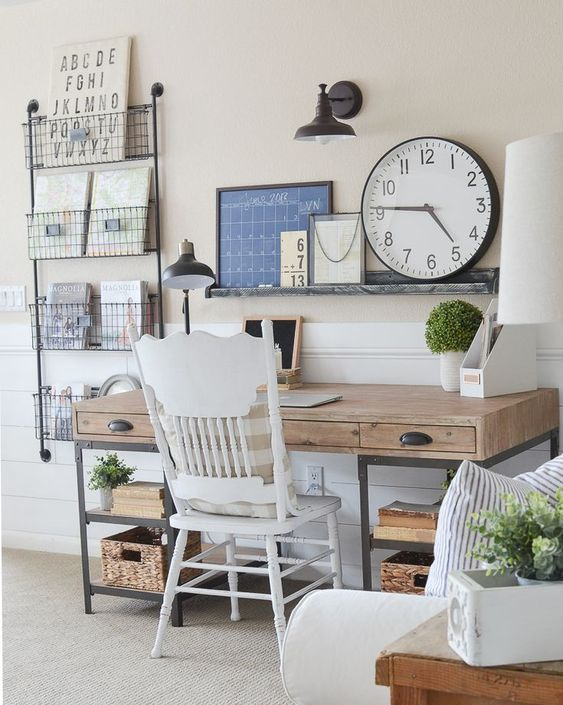a vintage farmhouse home office with a metal and wood desk, a vintage chair, a metal shelf with baskets and an open one over the desk