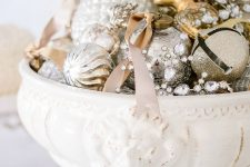 a vintage glam Christmas centerpiece of a beautiful bowl with metallic ornaments, crystals and gold glitter bells is a chic idea