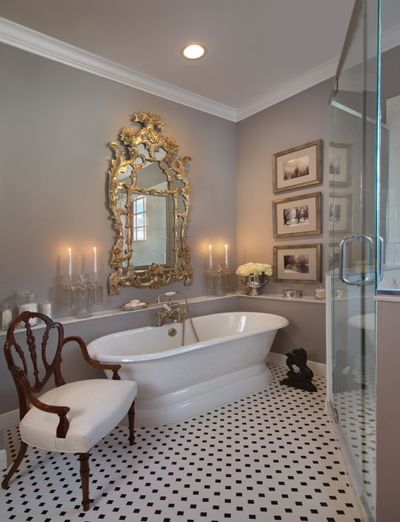 a vintage neutral bathroom with a refined mirror in a gold frame, a sophisticated chair, a gallery wall and printed floor