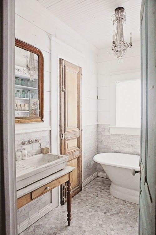 a vintage neutral bathroom with marble tiles of various shapes, a vintage vanity and a door, a crystal chandelier and a mirror in a wooden frame