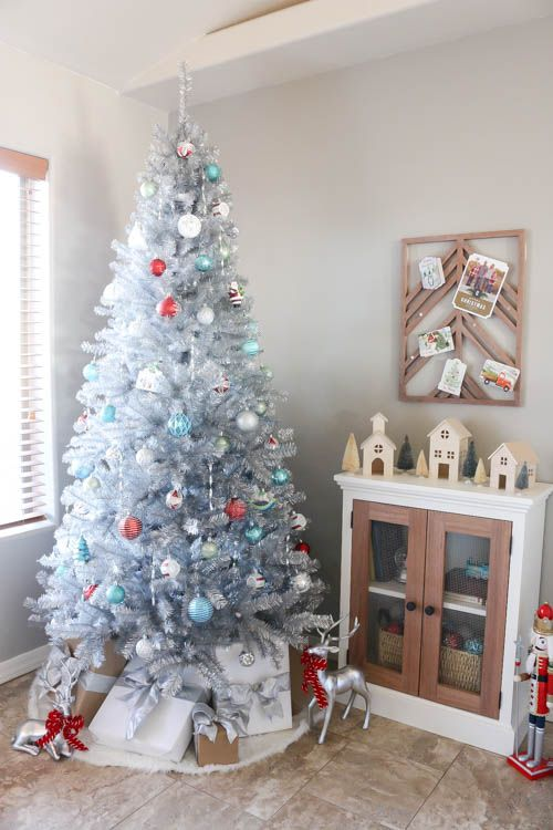 a vintage silver Christmas tree with blue, white and red ornaments and stacks of gift boxes and deer is a beautiful and refined idea