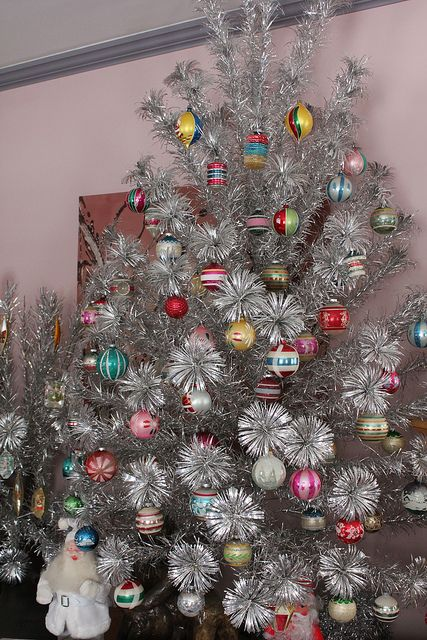 a vintage silver Christmas tree with bold vintage ornaments is a lovely and bright idea for vintage fans and it looks amazing