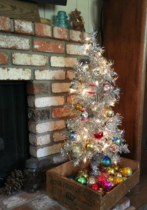 a vintage silver Christmas tree with lights, colorful ornaments, a vintage crate with ornaments is a lovely idea for refined holiday decor