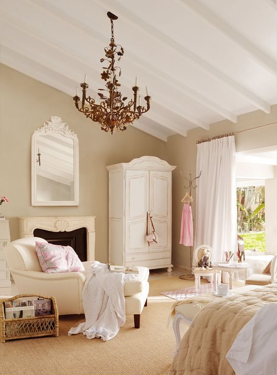 a warm neutral bedroom with buttermilk walls, vintage furniture, a vintage chandelier and touches of pink