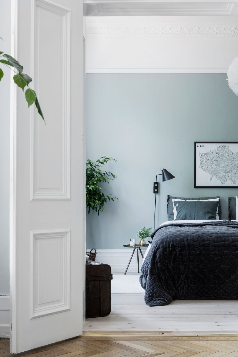 a welcoming Scandinavian bedroom with light green walls, a vintage chest for storage, a bed with dark bedding, black sconces and black nightstands