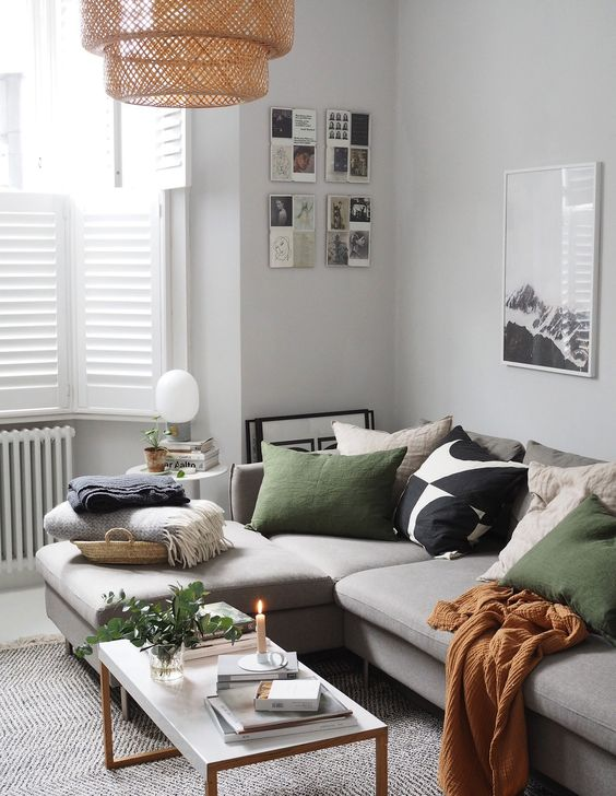a welcoming Scandinavian living room with a grey corner sofa, a woven lamp, some neutral pillows, a long table and black and white artworks