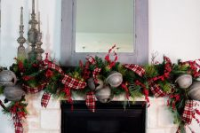a whimsical vintage mantel with a faux fir garland, plaid ribbons, oversized bells, vintage candleholders and some gift boxes