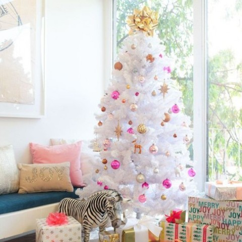 a cute white christmas tree with pink ornaments