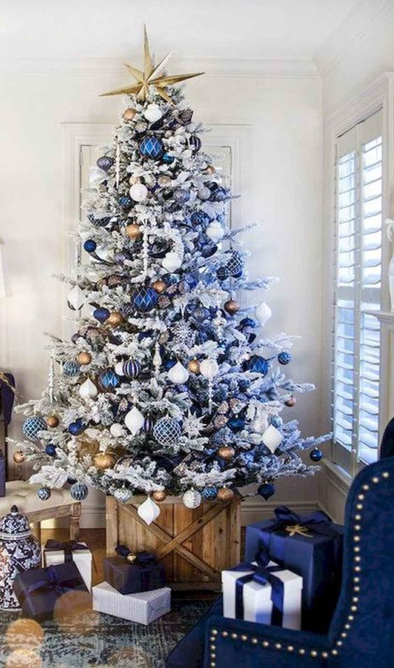 a white Christmas tree with navy, white, silver and blue ornaments, a gold star topper and icicles is very bold